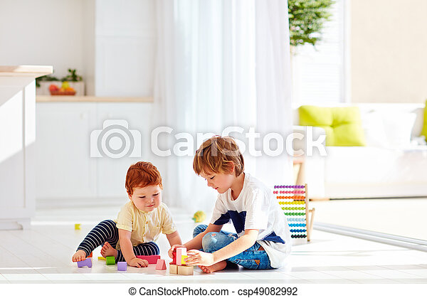 Elder Brother Playing With Little Baby Boy In Colorful Wooden Bricks At Home