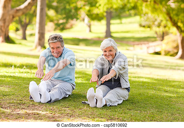 Elderly couple doing their stretches in the park - csp5810692