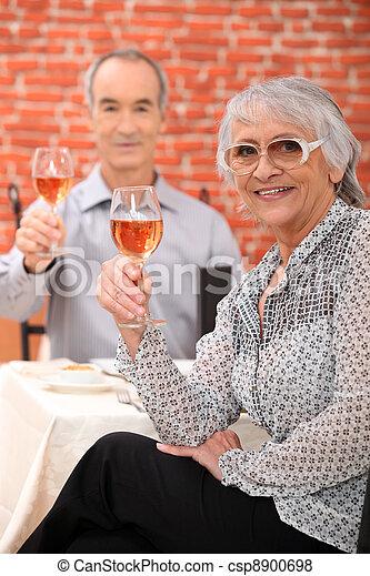 Elderly couple drinking wine in restaurant - csp8900698