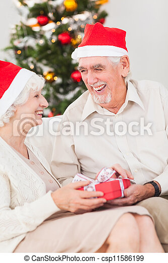 Elderly couple exchanging christmas gifts - csp11586199