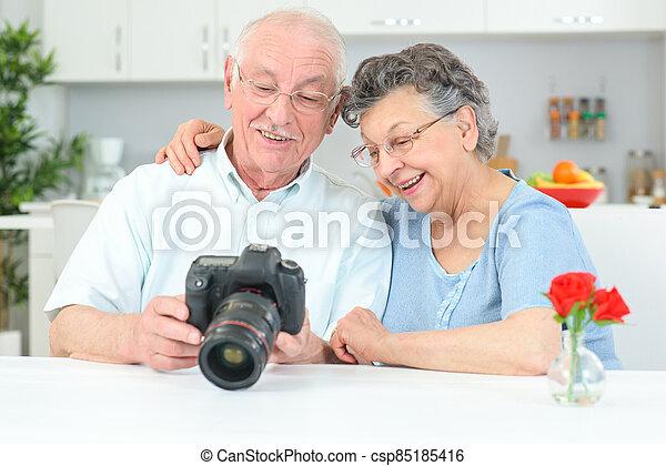 Elderly couple looking at photos on display of digital camera - csp85185416