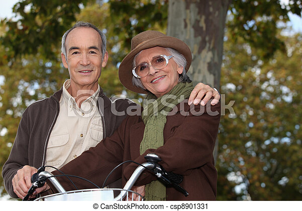 Elderly couple on a bike ride in the forest - csp8901331
