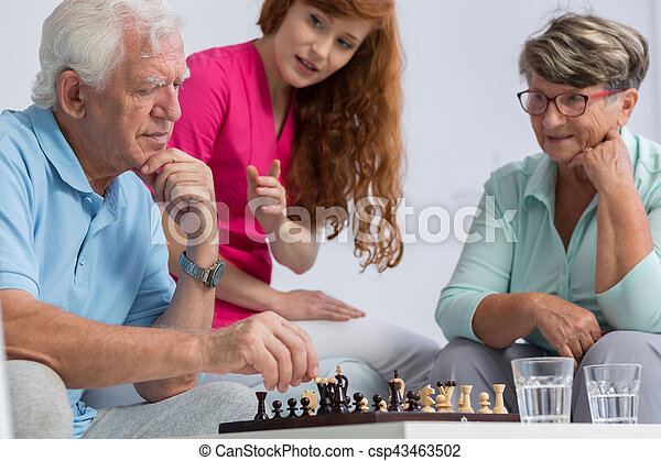 Elderly couple playing chess - csp43463502