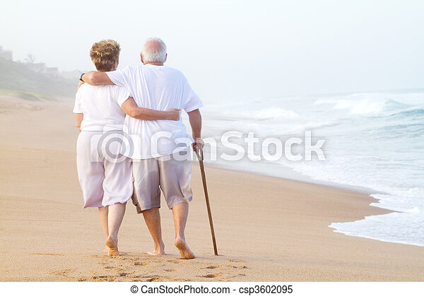 elderly couple strolling on beach - csp3602095