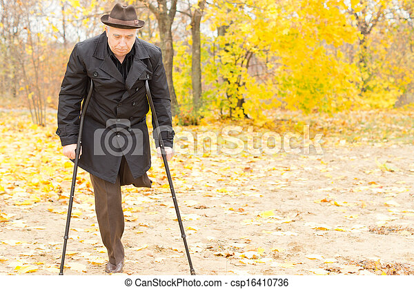 Elderly disabled man on crutches in a park - csp16410736