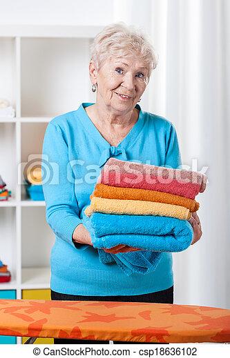 Elderly lady folding towels - csp18636102