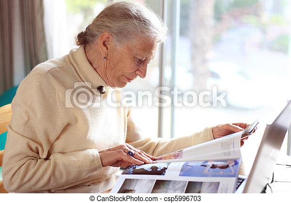 Elderly lady reading magazine. Shallow DOF. - csp5996703