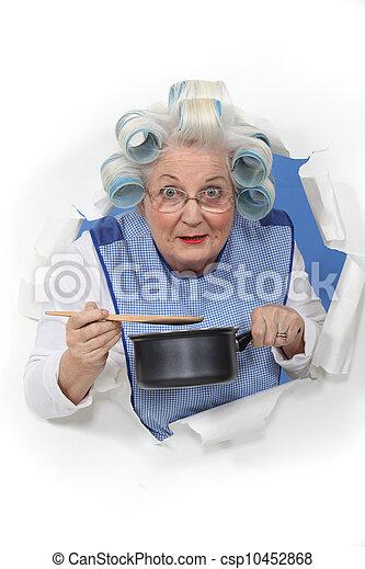 Elderly lady stirring sauce pan - csp10452868