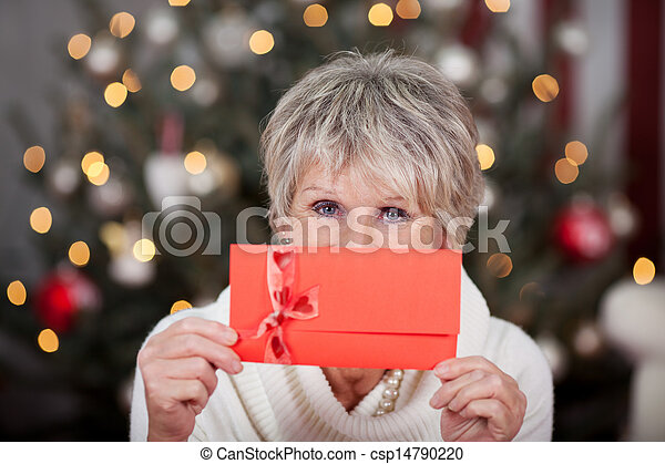 Elderly lady with a red gift voucher - csp14790220