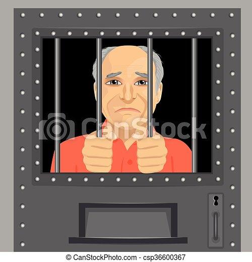 elderly man looking from behind bars - csp36600367