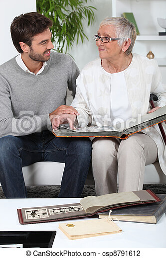 Elderly person looking at photos with son - csp8791612
