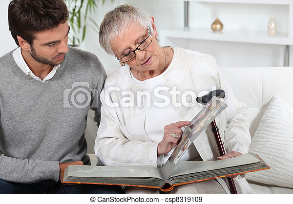 Elderly person looking at photos with son - csp8319109