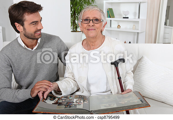 Elderly person looking at photos with son - csp8795499