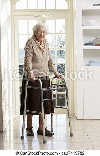 Elderly Senior Woman Using Walking Frame - csp7413782