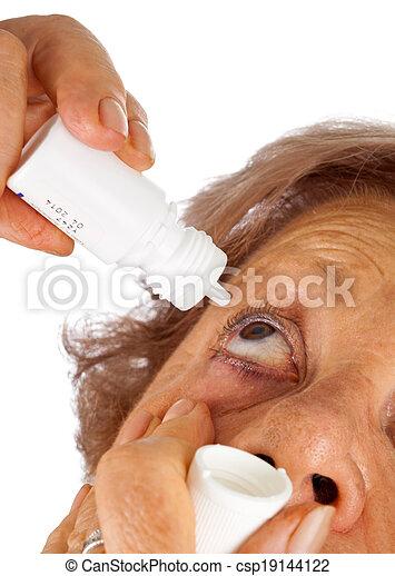 Elderly woman applying eye drops - csp19144122