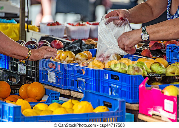 Elderly woman buying fruits on the market. - csp44717588