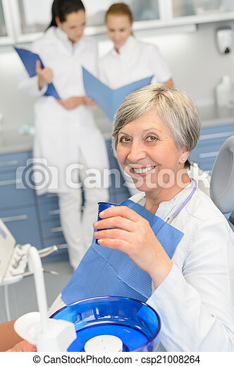 Elderly woman dentist team at dental surgery - csp21008264