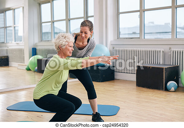 Elderly woman doing exercise with her personal trainer - csp24954320
