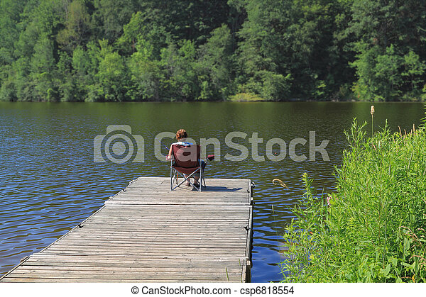 Elderly woman fishing from the dock.  - csp6818554