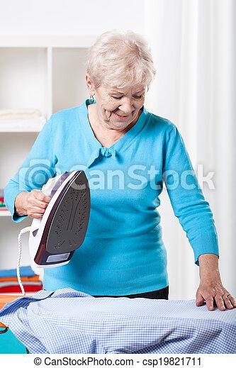 Elderly woman ironing - csp19821711