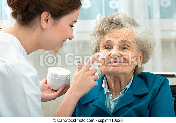 Elderly woman is assisted by nurse at home - csp21110620