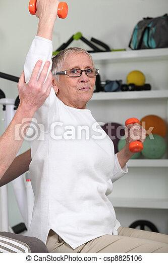 Elderly woman lifting dumbbells - csp8825106