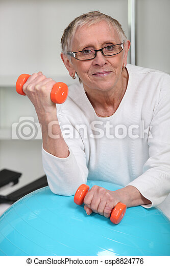 Elderly woman lifting weights in gym - csp8824776