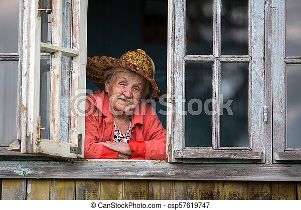 Elderly woman looking from the window of the farmhouse. - csp57619747
