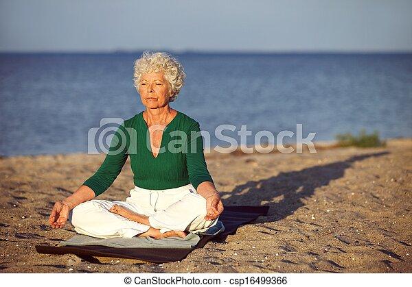 Elderly woman on beach meditating by ocean - csp16499366