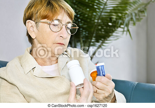 Elderly woman reading pill bottles - csp1627120