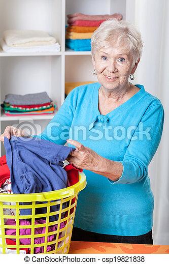 Elderly woman sorting laundry - csp19821838