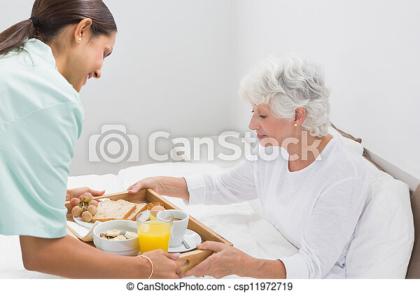 Elderly woman taking a breakfast with home nurse - csp11972719