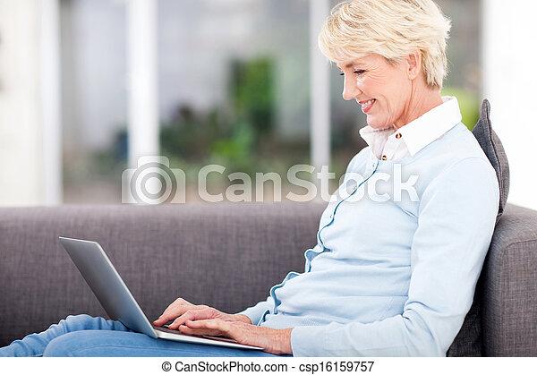 elderly woman using laptop computer - csp16159757