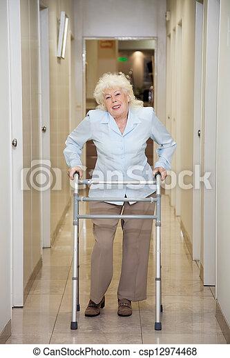 Elderly Woman With Walker In Hospital Corridor - csp12974468