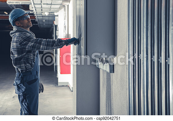 Electric Installation Technician In Front of Main Fuse Box - csp92042751