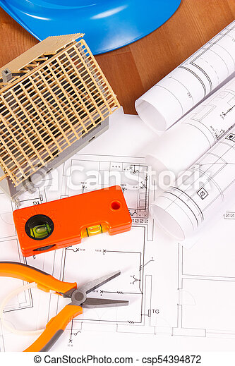 Electrical diagrams, orange work tools, blue helmet for engineer jobs and house under construction, building home concept - csp54394872