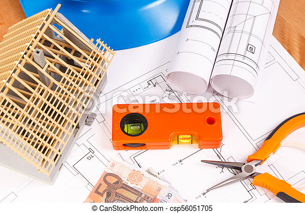 Electrical diagrams, work tools for engineer jobs, house under construction and currencies euro on desk in office - csp56051705