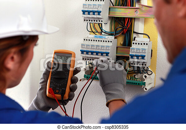 electrician and his apprentice working on a fuse board - csp8305335