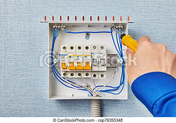 electrician install a fusebox or circuit breakers. the installer installs  an electrical switchgear in the house. mounting the  can stock photo