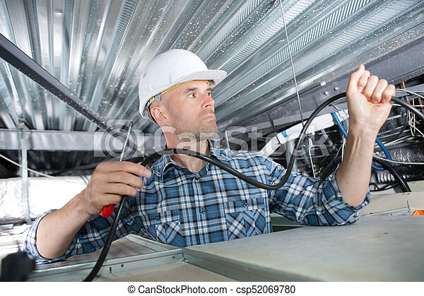 Electrician installing cables in roof