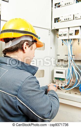 Electrician installing energy saving meter - csp9371736