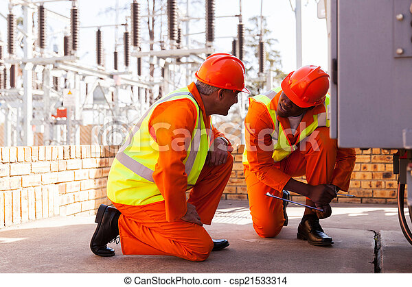 electricians discussing work in electrical substation - csp21533314