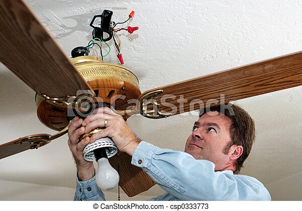 El electricista quita el ventilador del techo - csp0333773