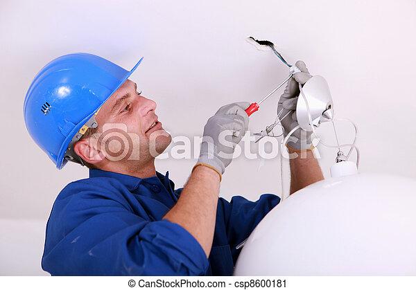 Electricista cableando una luz del techo - csp8600181