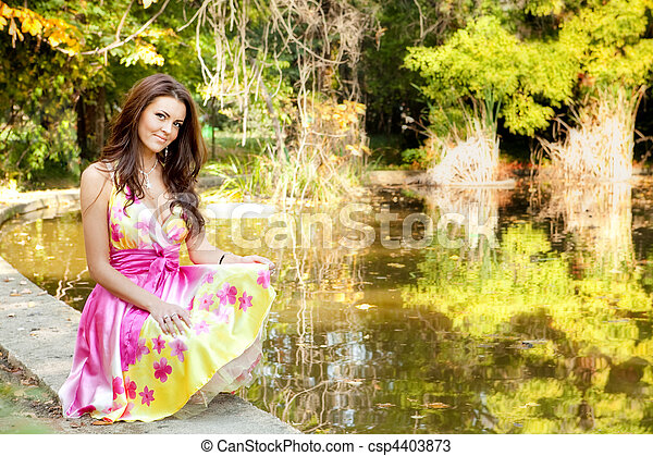 Elegant beautiful woman with colorful dress outdoor - csp4403873
