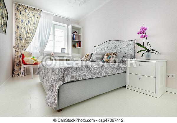 Elegant bedroom in soft light colors, big bed at center.