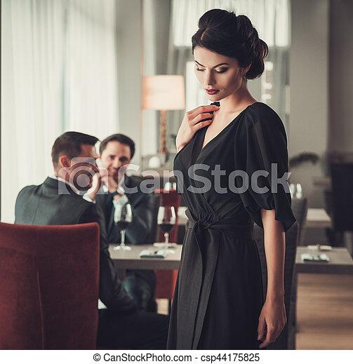 ddd92a8f4 Elegant brunette lady in black evening dress in restaurant.