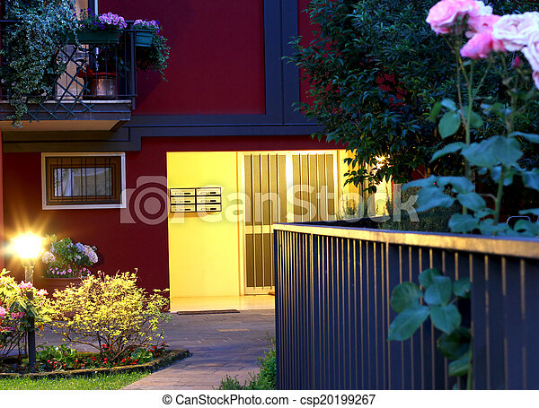 elegant entry of a luxury home at night with lamp and roses - csp20199267