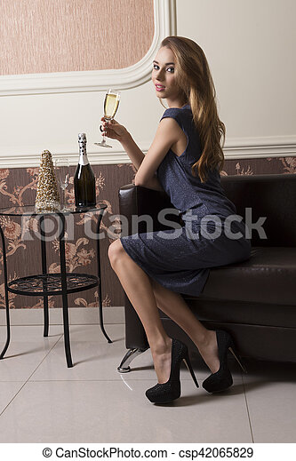9794ecbe9d48 Elegant girl drinking champagne. Elegant woman with blue dress and ...
