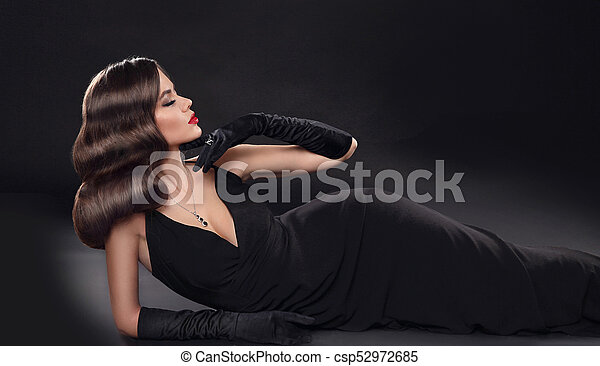 4f50a11bf Elegant lady in long sexy dress with retro wavy hairstyle lying isolated on  studio black background. Beautiful brunette woman in glamour gloves. ...